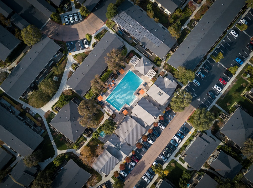 aerial view of blue pool near parking area at daytime