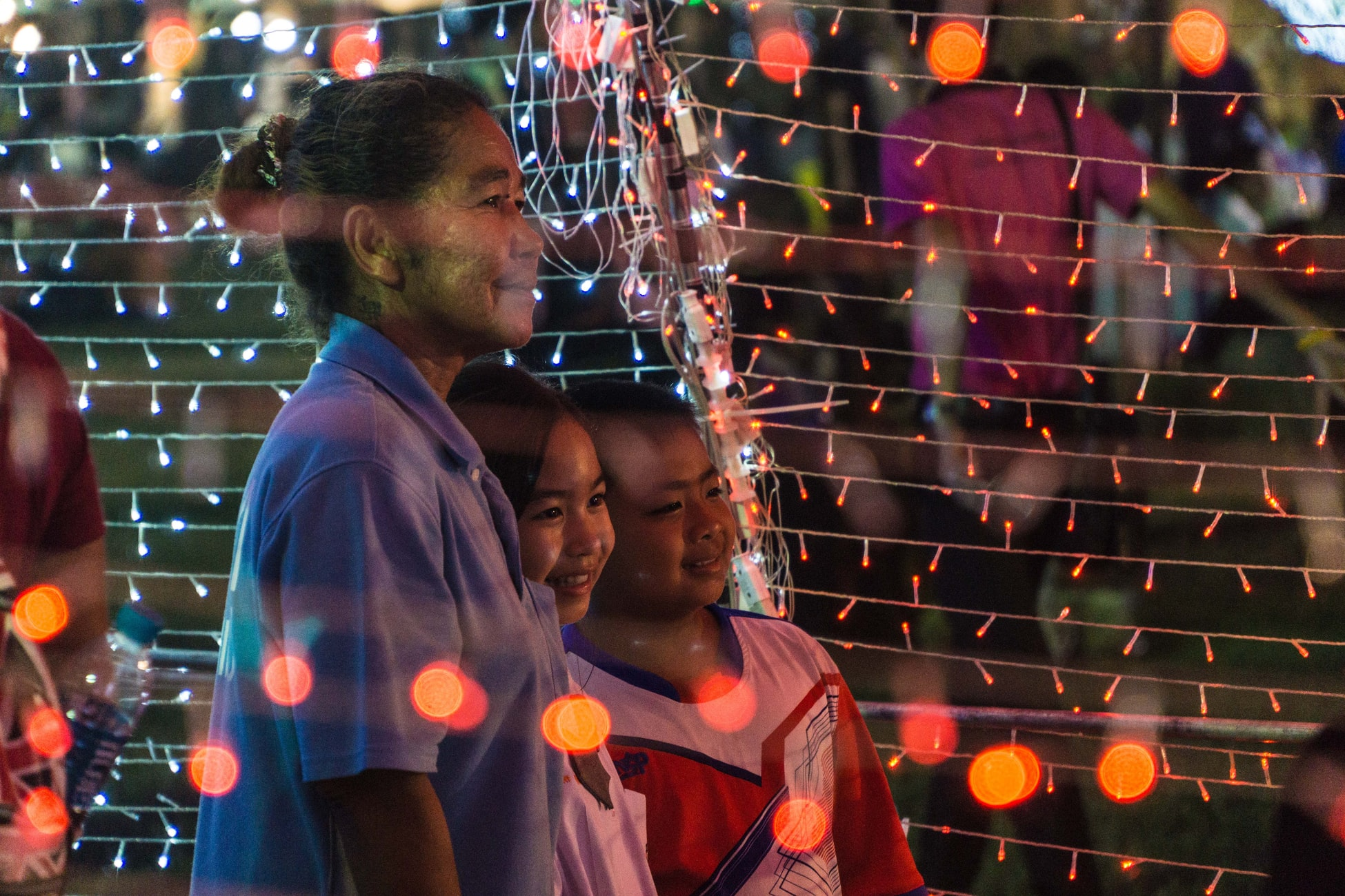 A photo of an elderly woman with children standing next to her at a street festival of some kind. She is looking out at something with a contented smile on her face. There are lights all around.