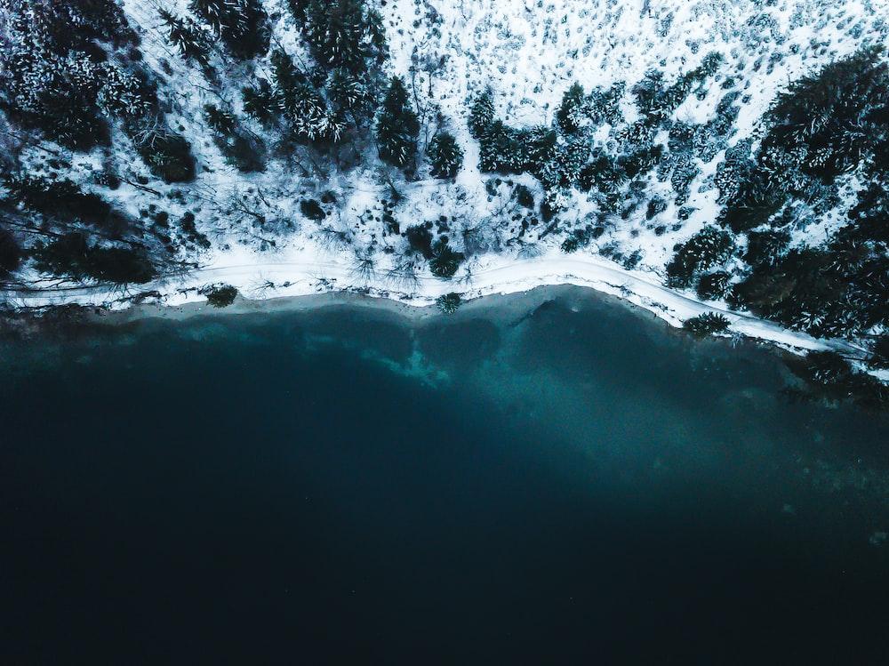 body of water near snowy mountain