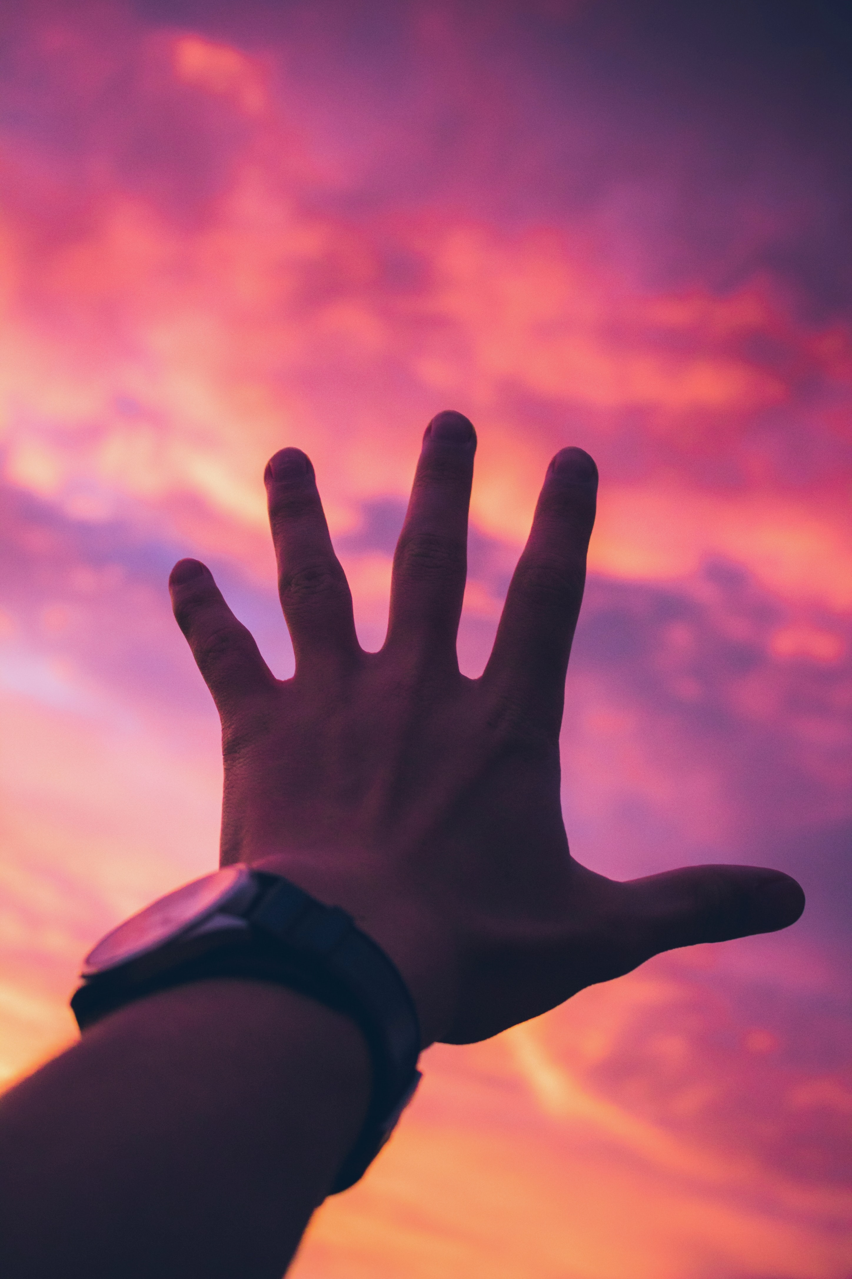 person with black watch reaching for orange sky
