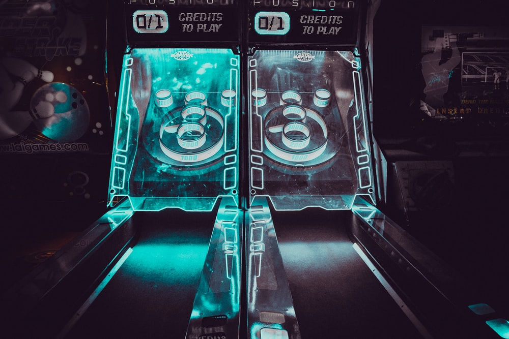 two black-and-blue lighted skeeball tables