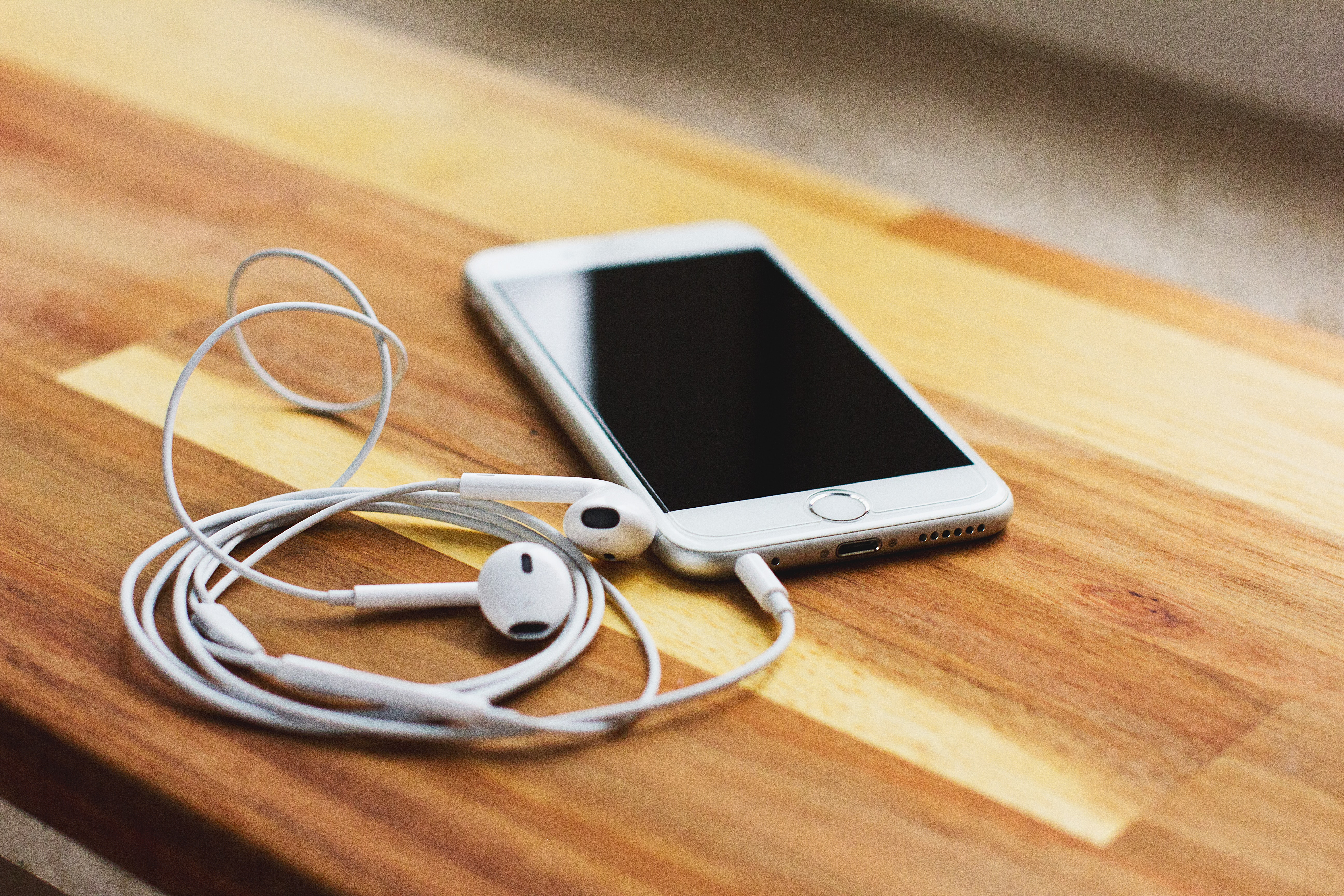 silver iPhone 6 with EarPods on brown wooden table