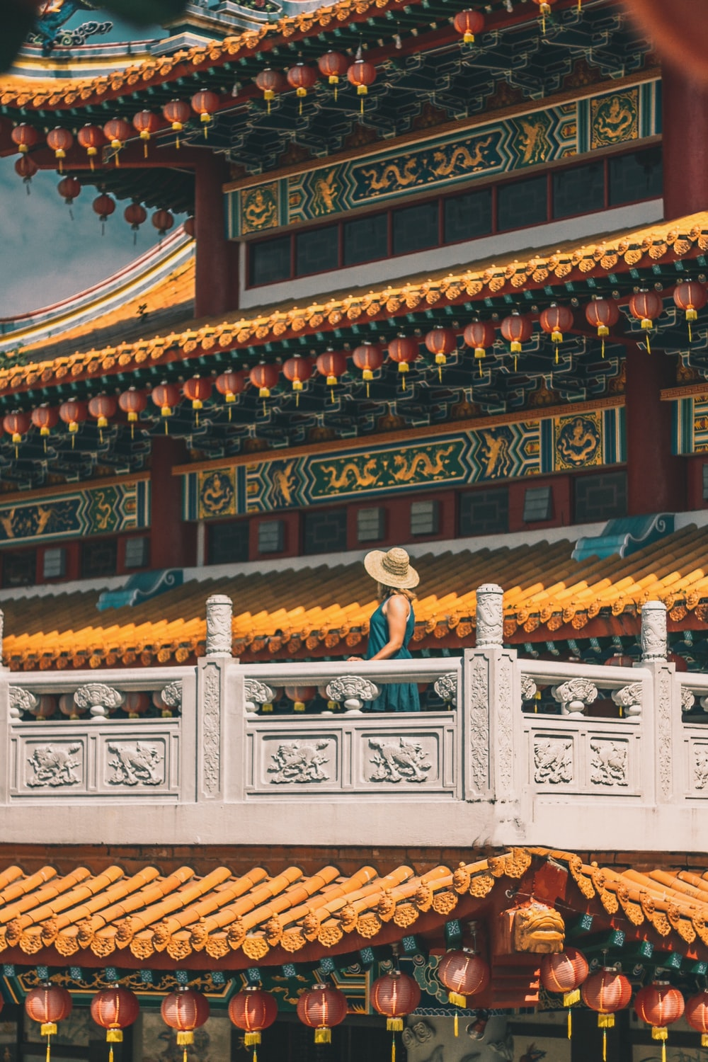 woman standing on gray patio of pagoda during daytime