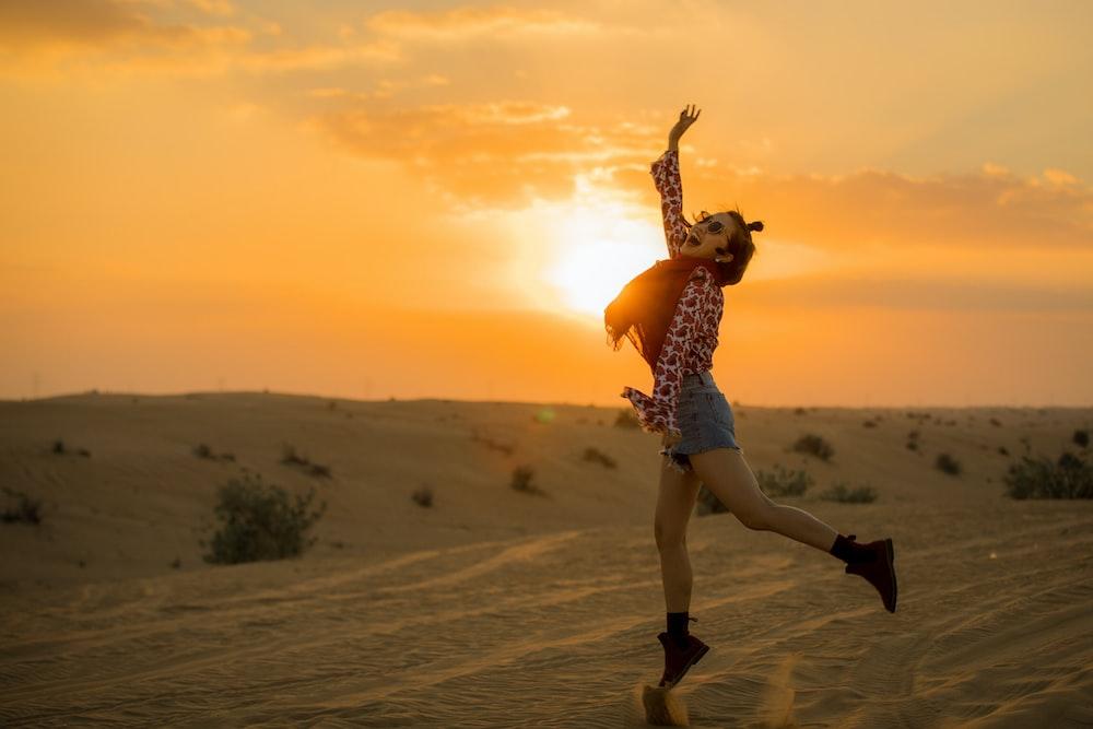 woman jumping on desert during golden hour
