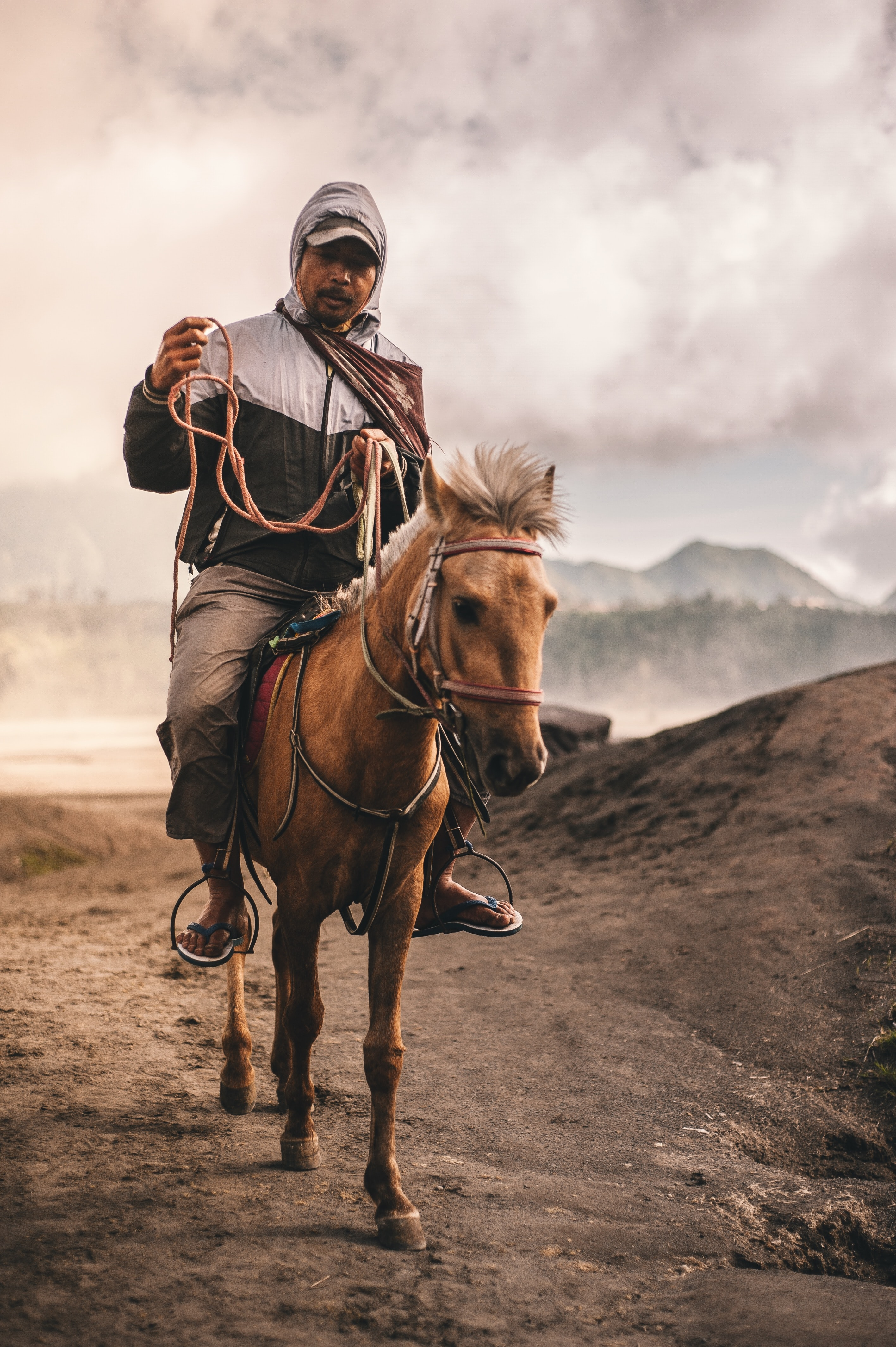 man riding horse under cloudy skies