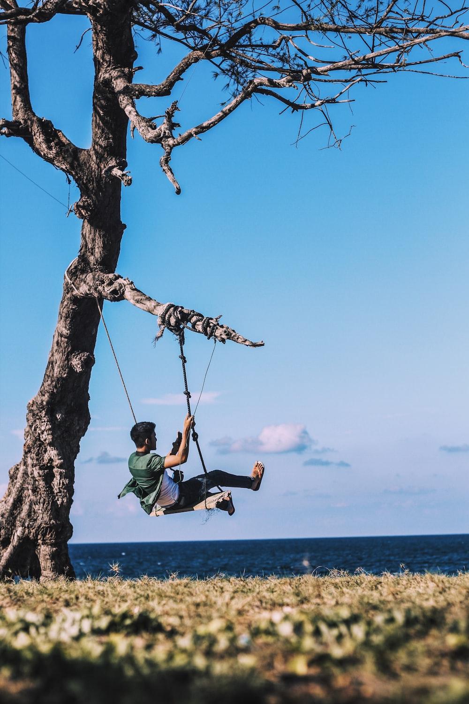 man on swing mounted on tree near body of water