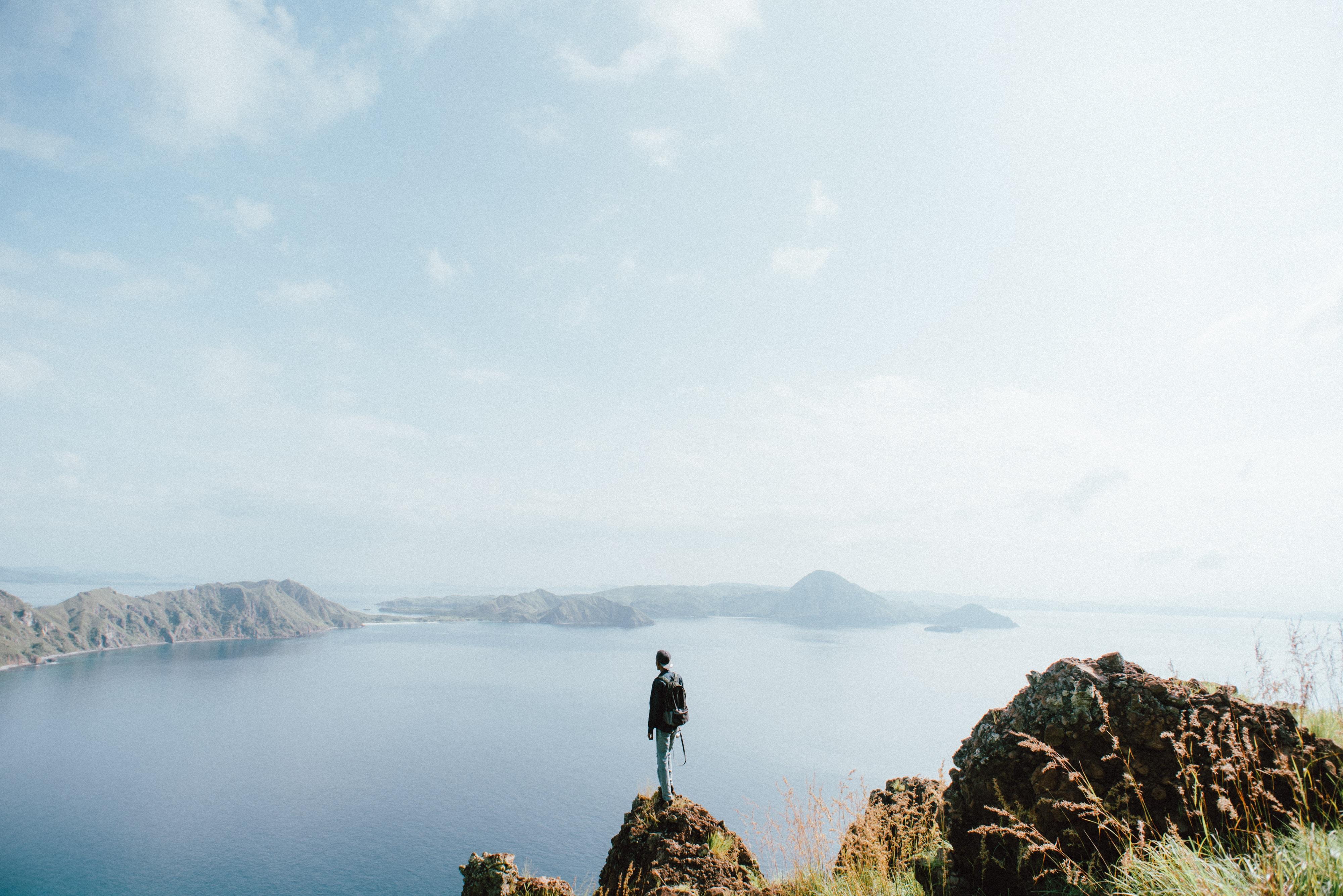 man standing on brown stone during daytime