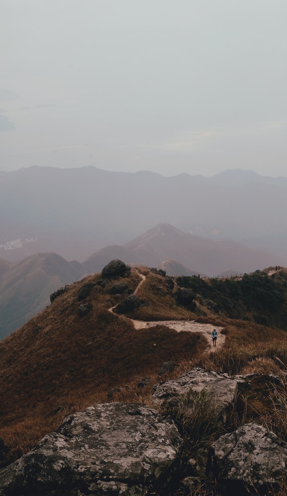 man waking across winding road near mountain ranges