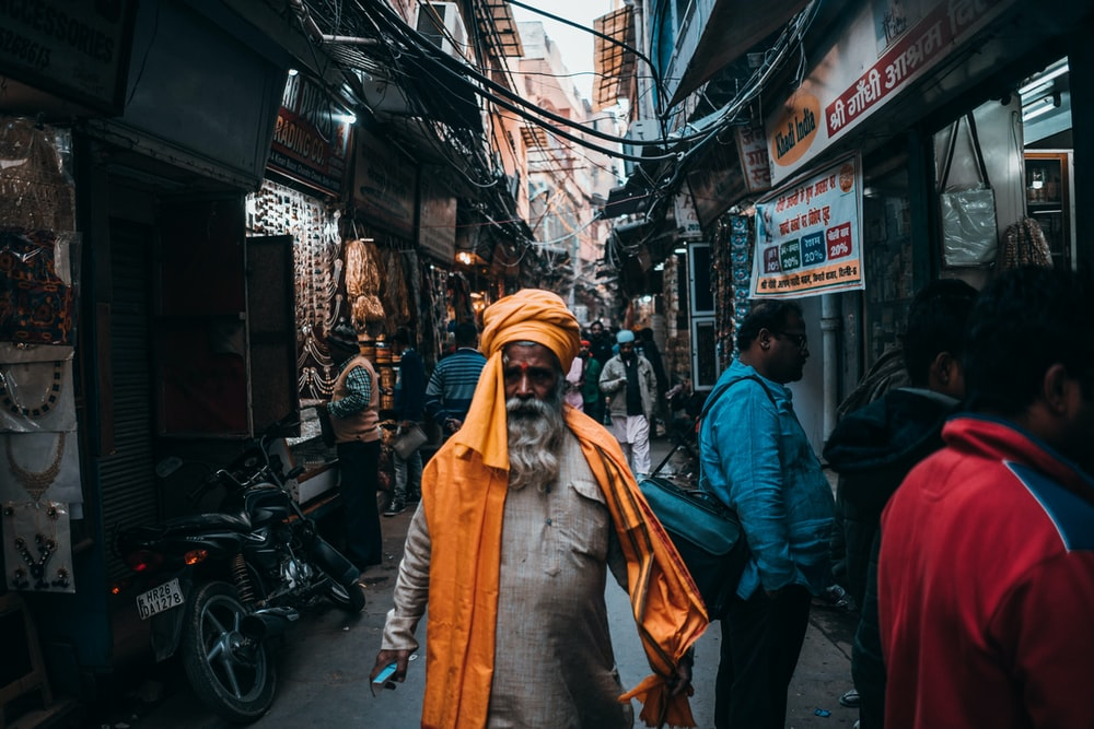 man in orange turban standing in middle of road