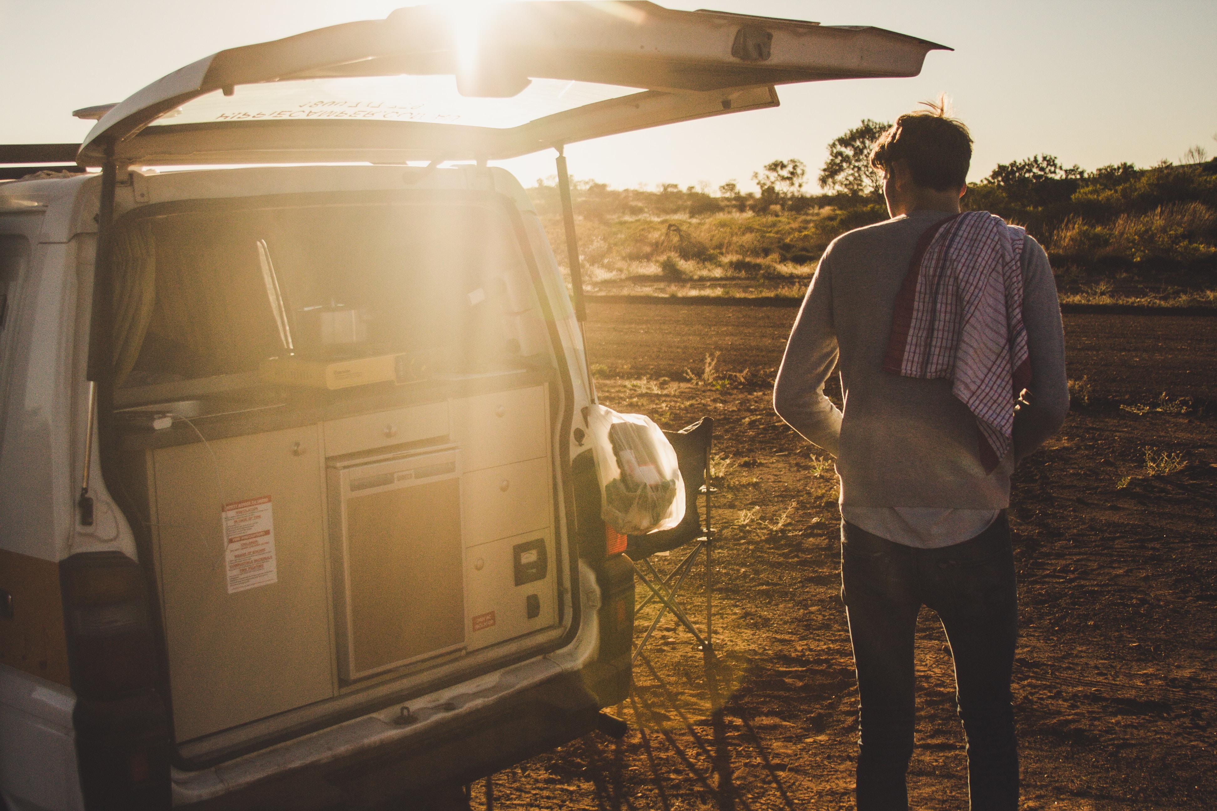 man standing near white van during daytime