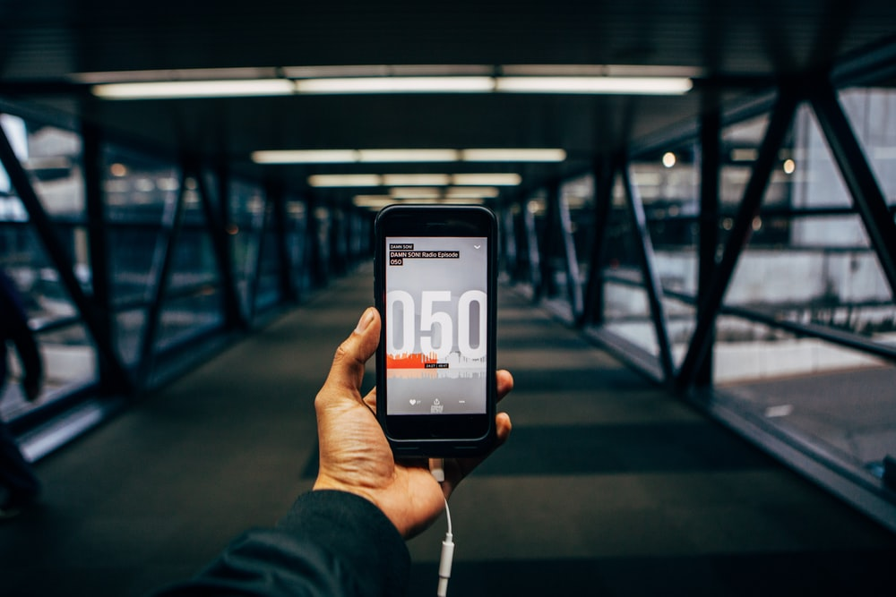 person holding black smartphone while standing on bridge