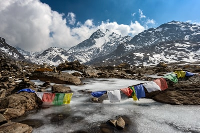 assorted-color of apparel hanged below creek across glacier mountain nepal zoom background