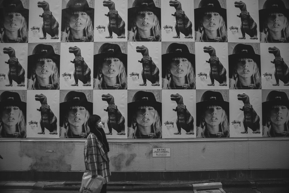 grayscale photo of person looking at the wall
