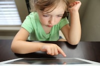 girl sitting beside the table while operating tablet computer