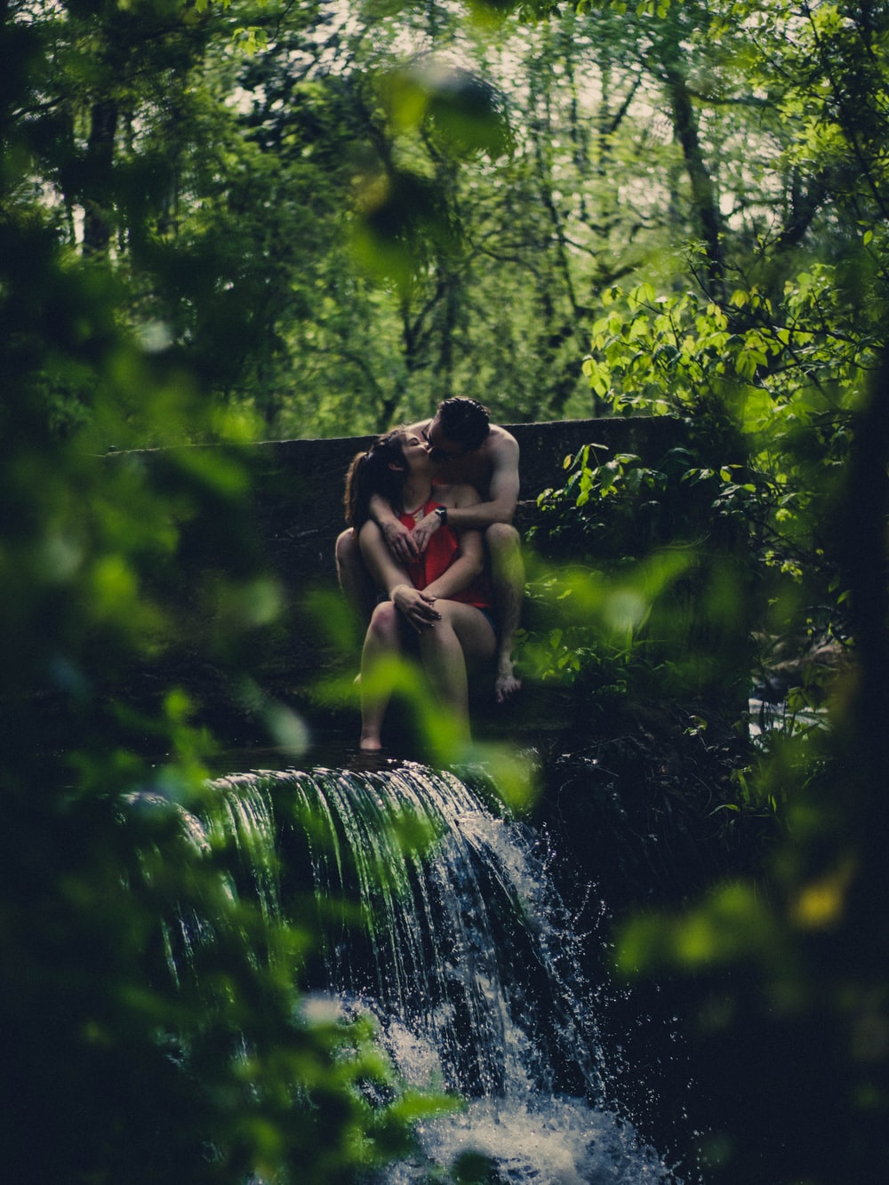 couple kissing on waterfalls in forest during daytime