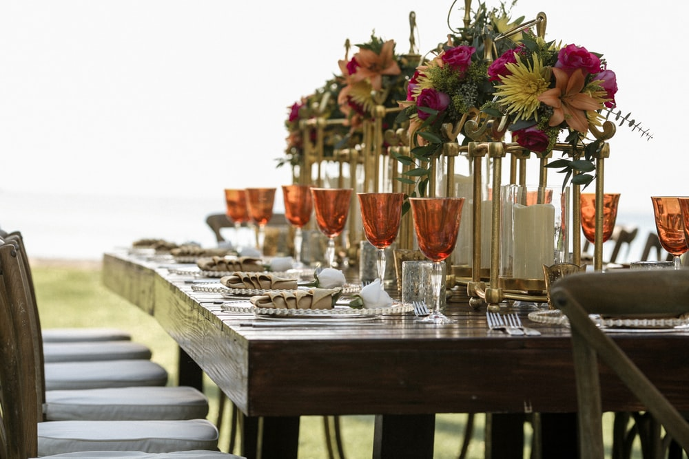 orange tinted wine glasses on rectangular brown wooden dining table