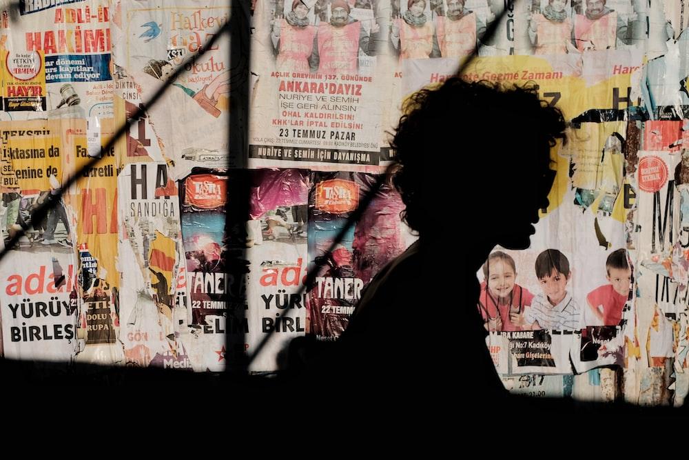 silhouette of person near magazine wall