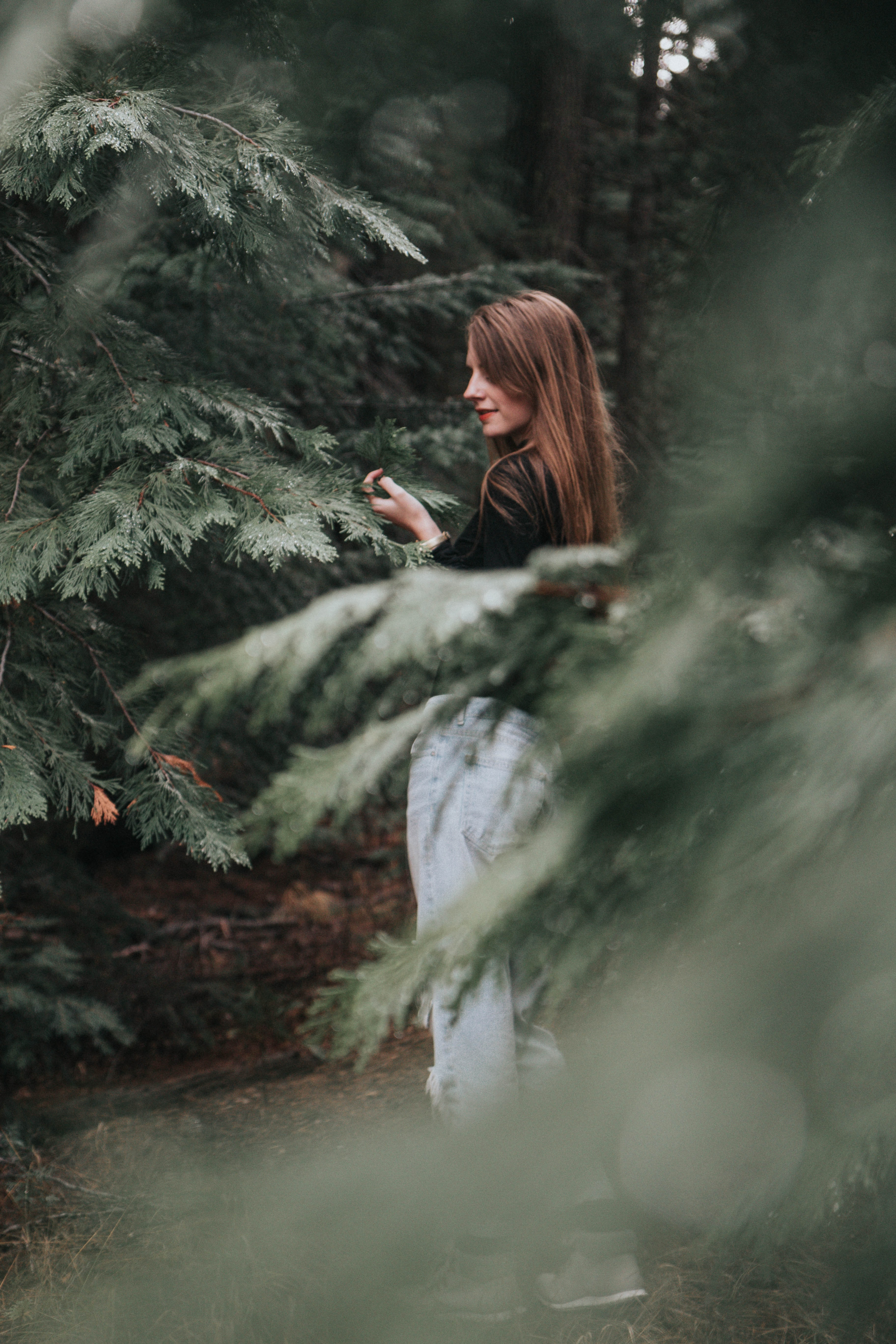 selective focus photography of woman standing between trees