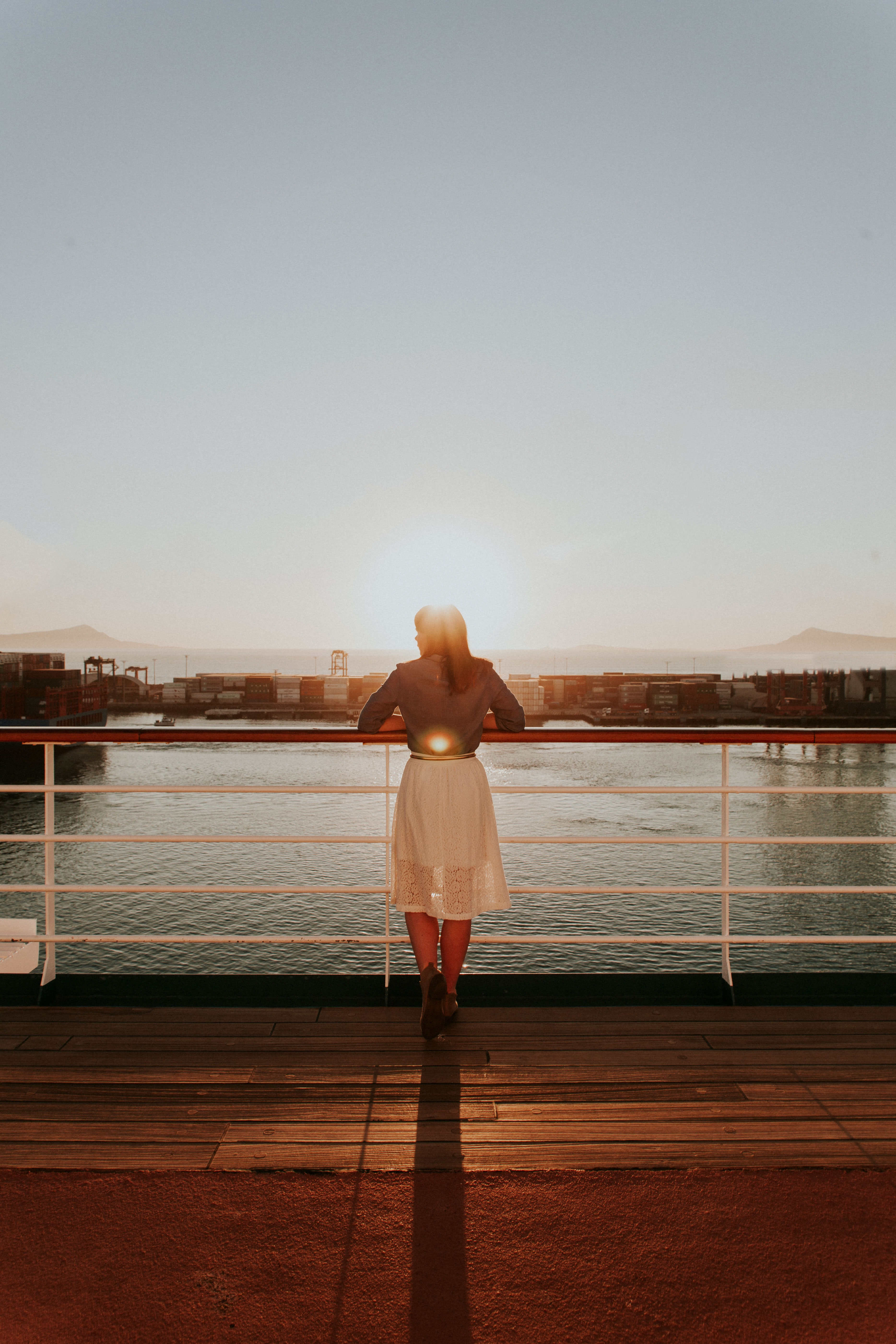 woman wearing white skirt looking at body of water during daytime