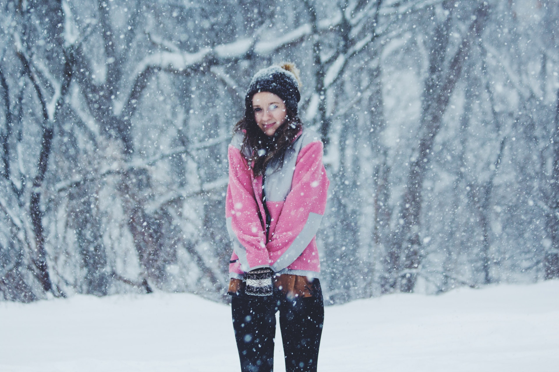 woman wearing pink jacket standing on snow ground