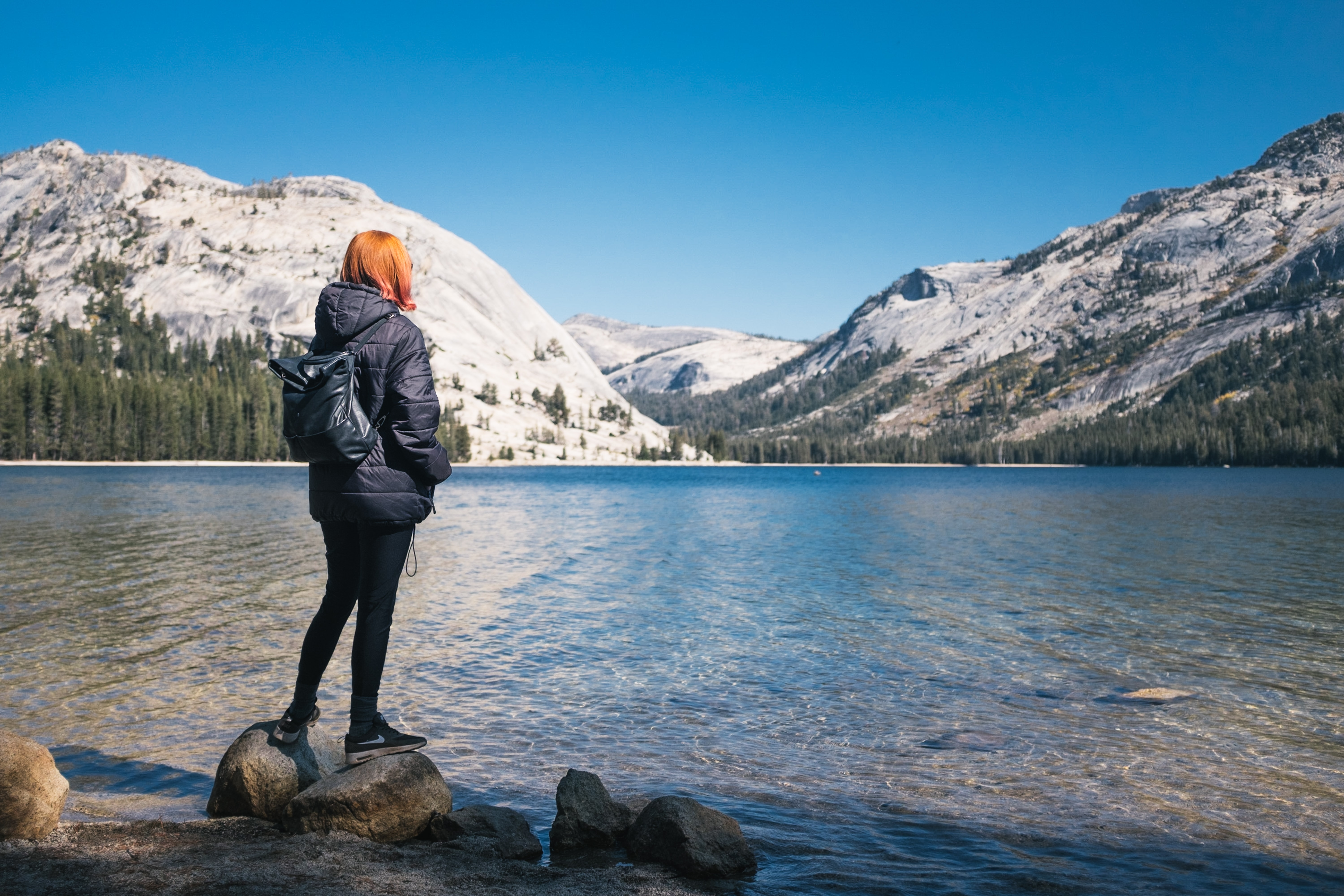 woman wearing black bubble jacket beside lake near hills covered with snow during daytime