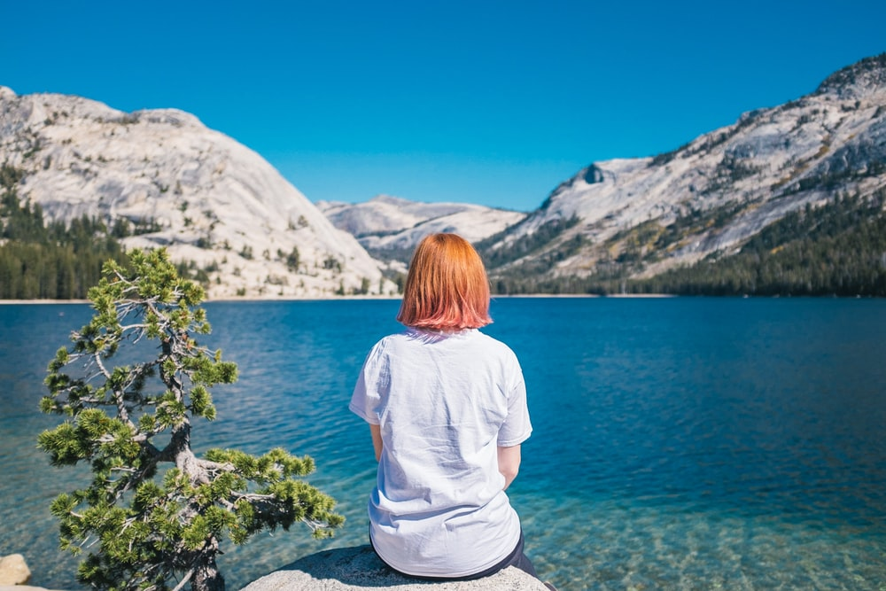 woman sitting on the stone facing the ocean and mountain
