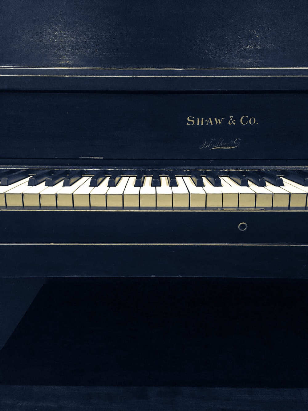 black and white Shaw and Co. upright piano