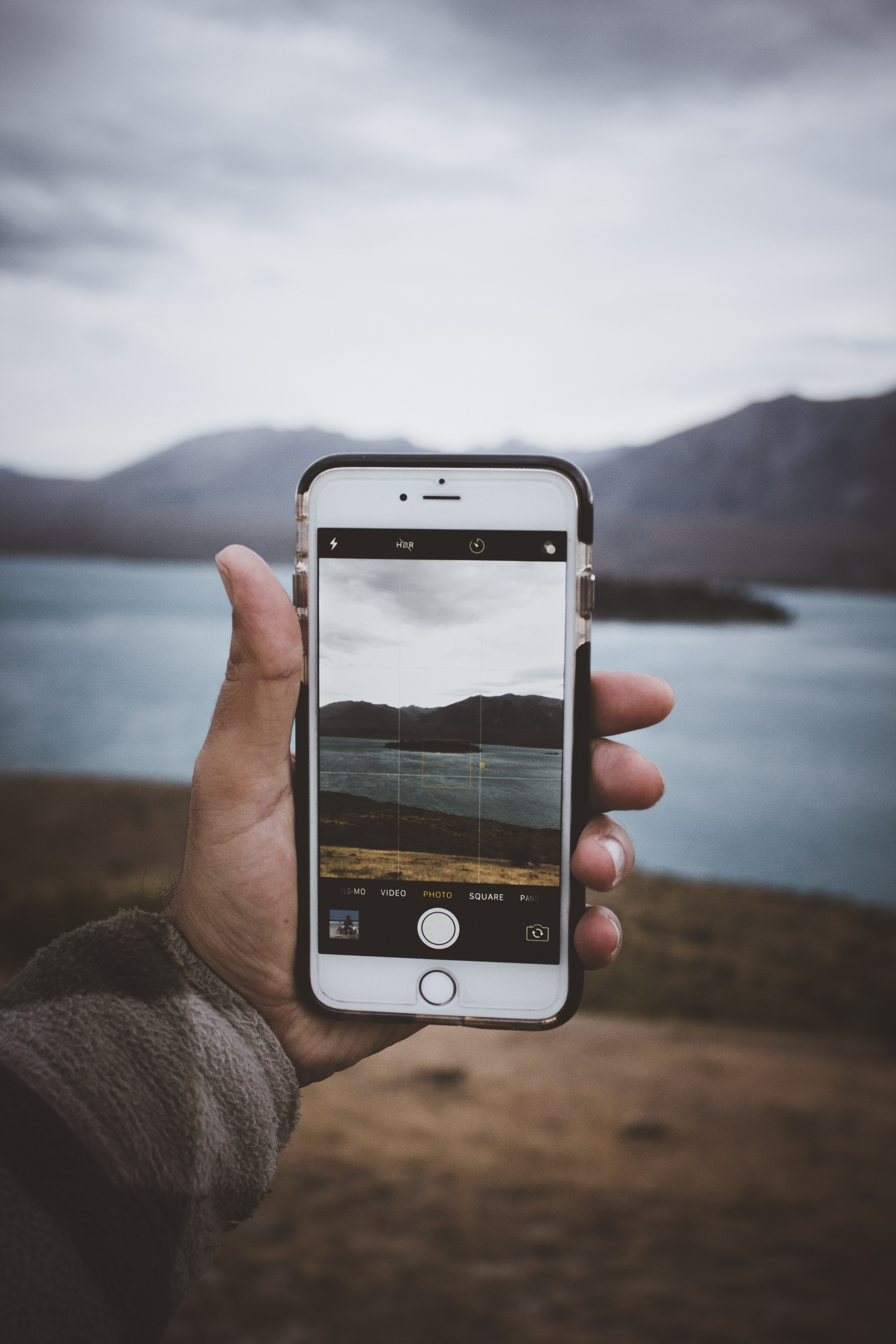 person holding gold iPhone 6 taking a photo of lake surrounded island during daytime