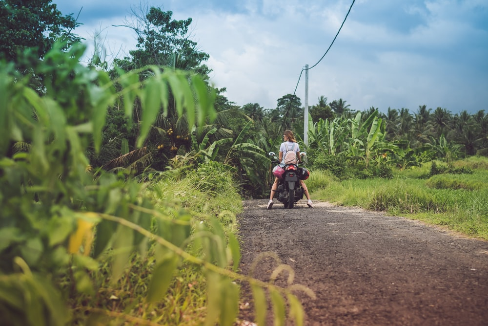 woman on motorcycle on road under cloudy sky during daytime