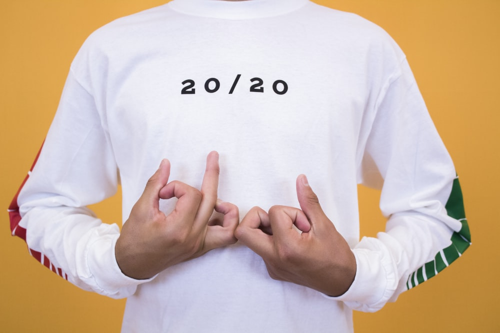 man in white and black 20/20 printed crew-neck sweatshirt making handsigns