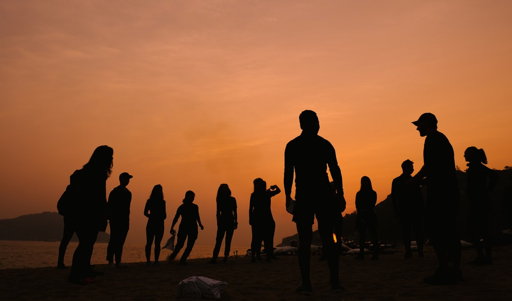 silhouette of people under cloudy sky