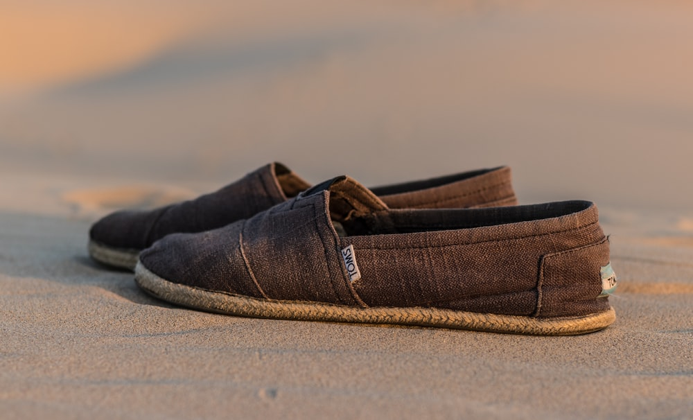 pair of brown Toms loafers on brown sand
