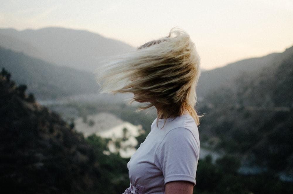 woman wearing white t-shirt near mountain during daytime