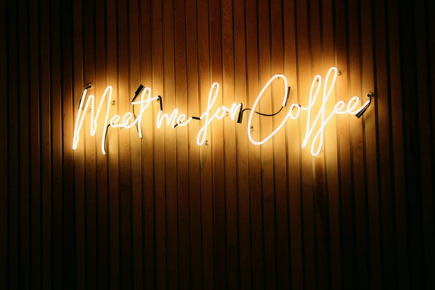 """A yellow neon sign reads: """"Meet me for coffee"""""""