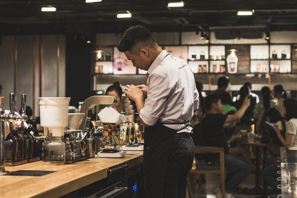 men's brown dress shirt and black pants making drinks inside a bar