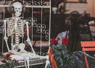 human skeleton wearing headphones while sitting in white steel egg chair