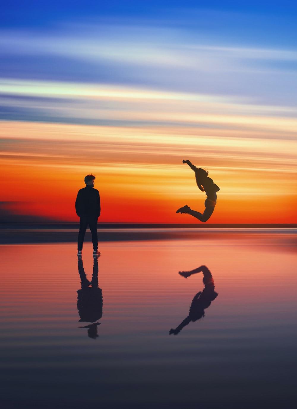man near woman jumping near body of water
