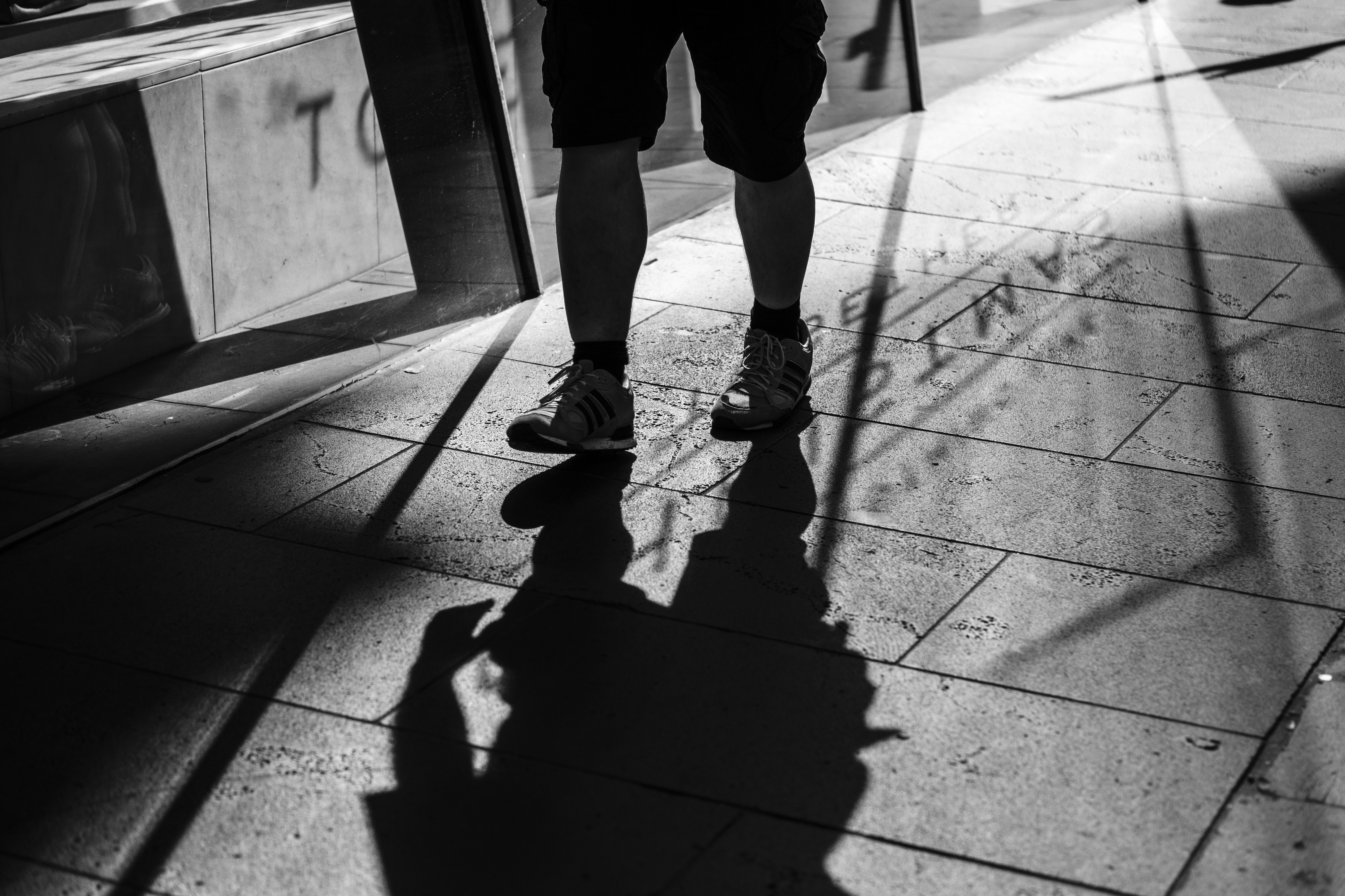 person standing on concrete pavement against the light