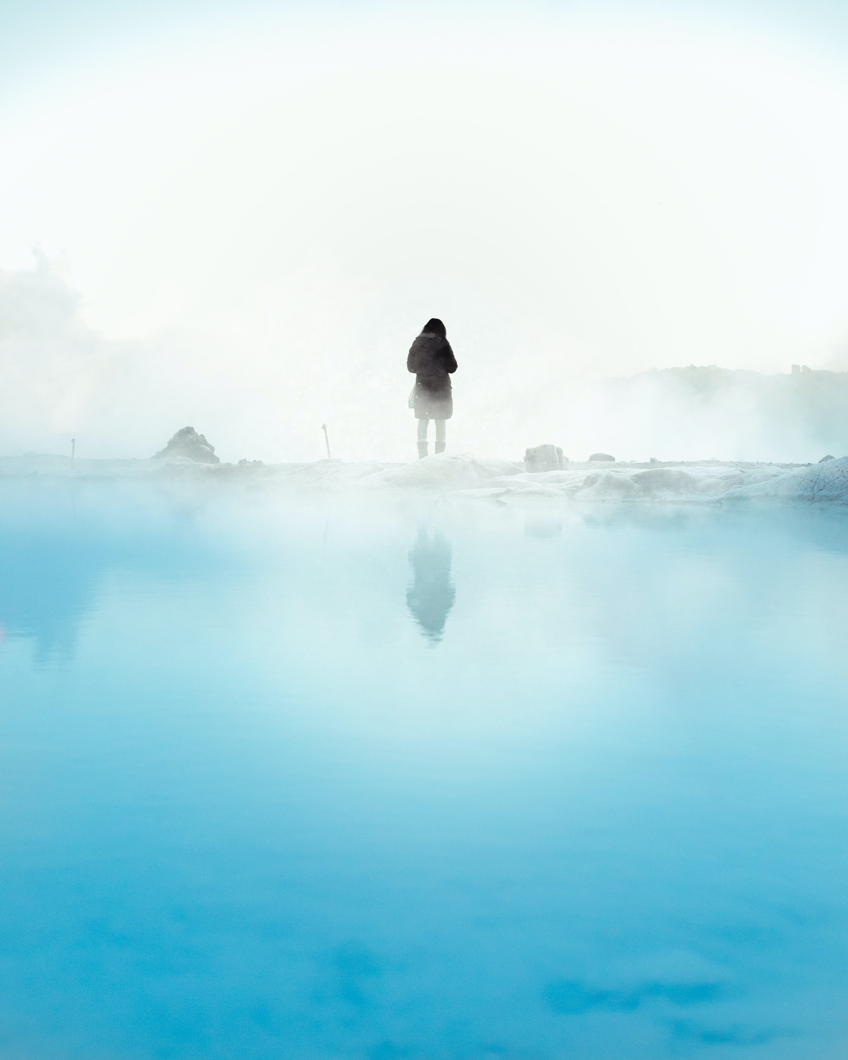 person standing beside body of water during daytime