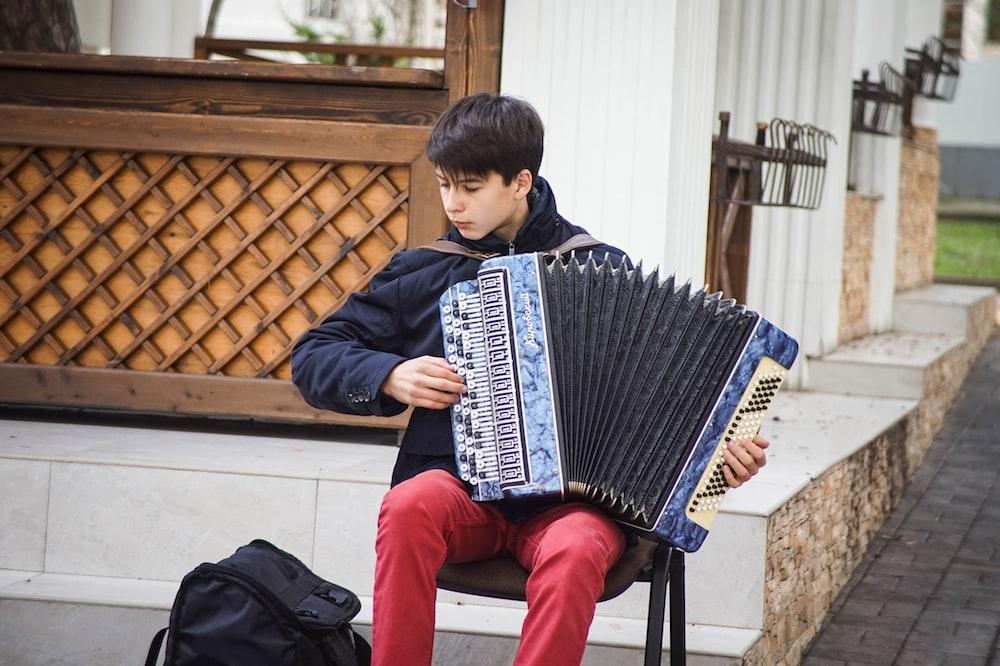 man playing blue accordion during daytime