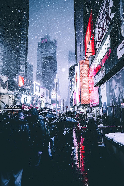 people holding umbrella between building