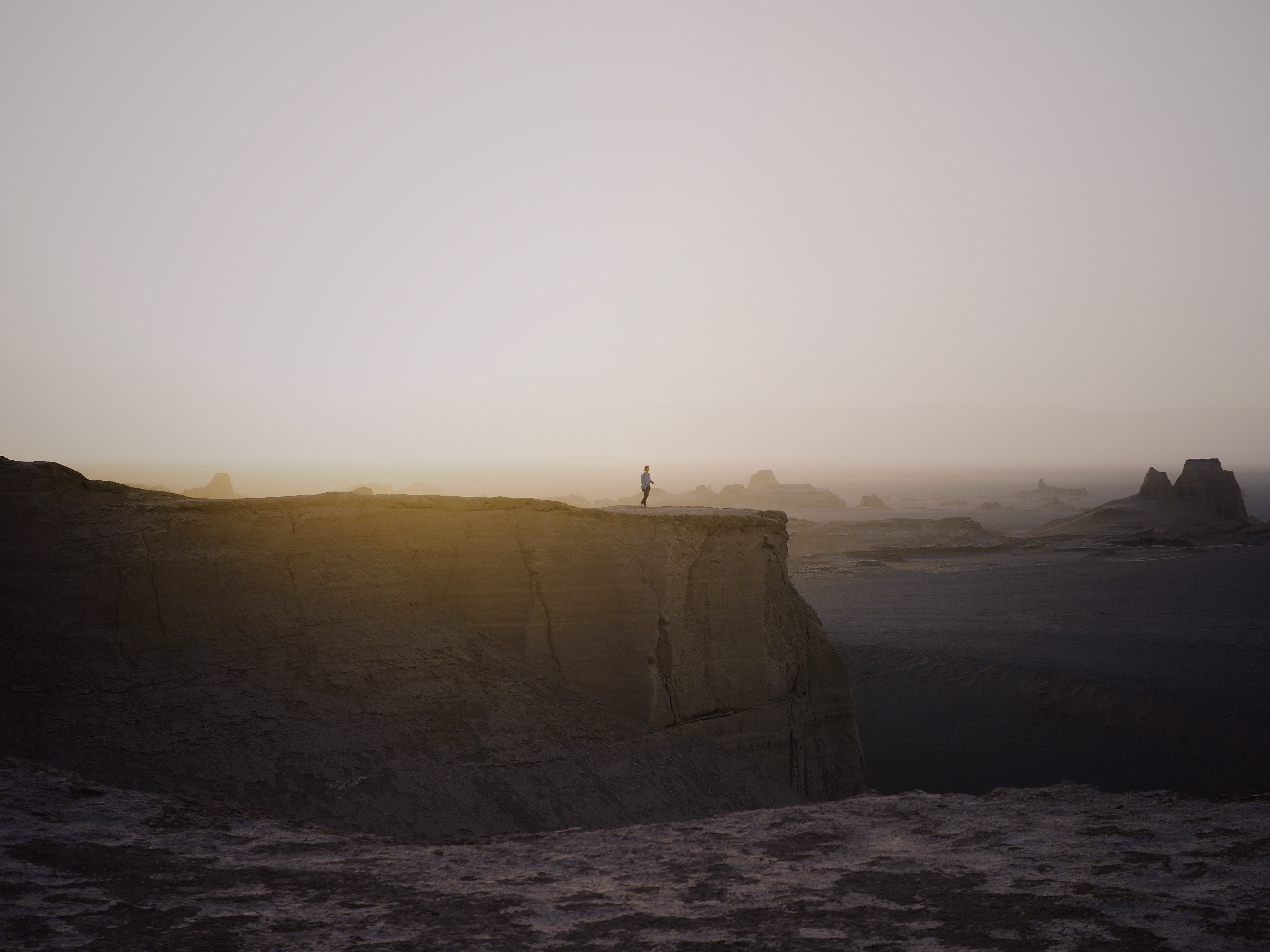 person standing on cliff under white sky