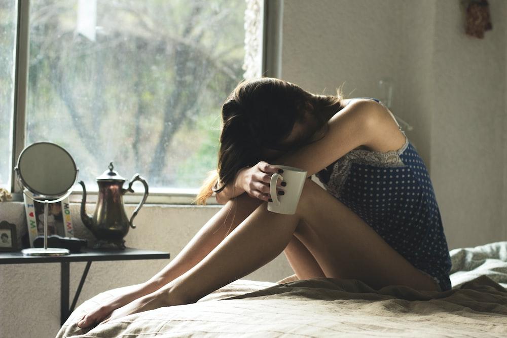 woman sitting on bed while holding mug