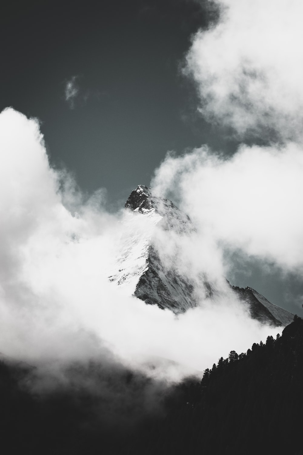 grayscale photo of mountain covered in clouds
