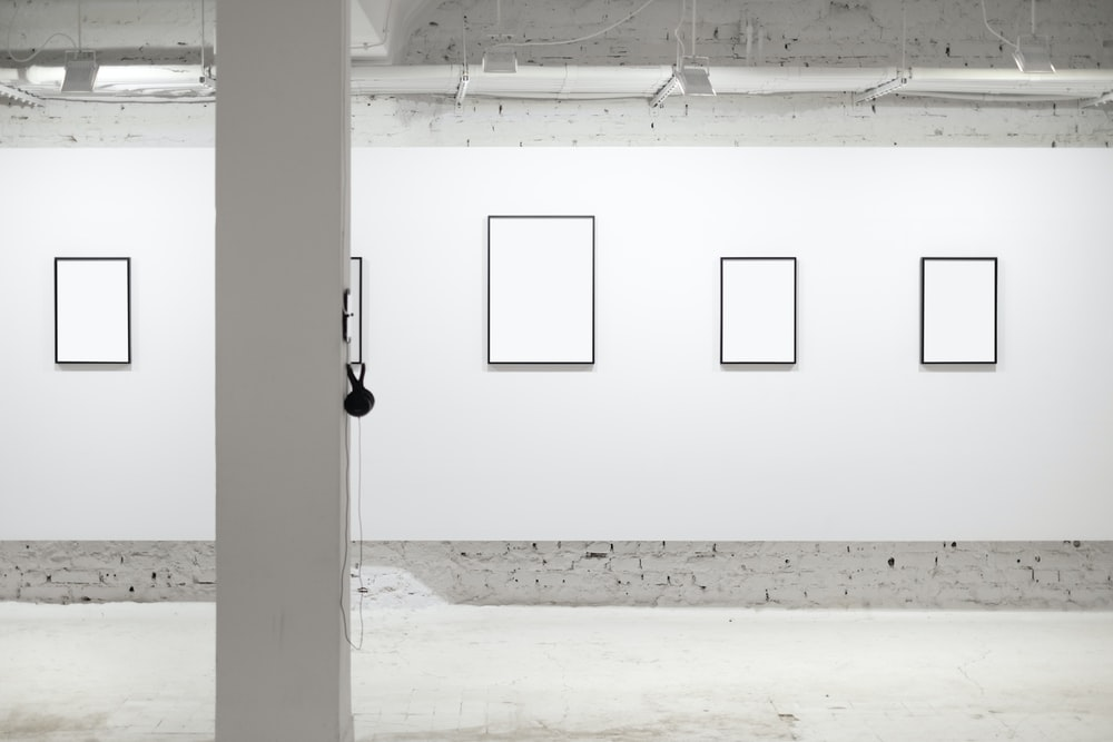 four white wall photo frames in room