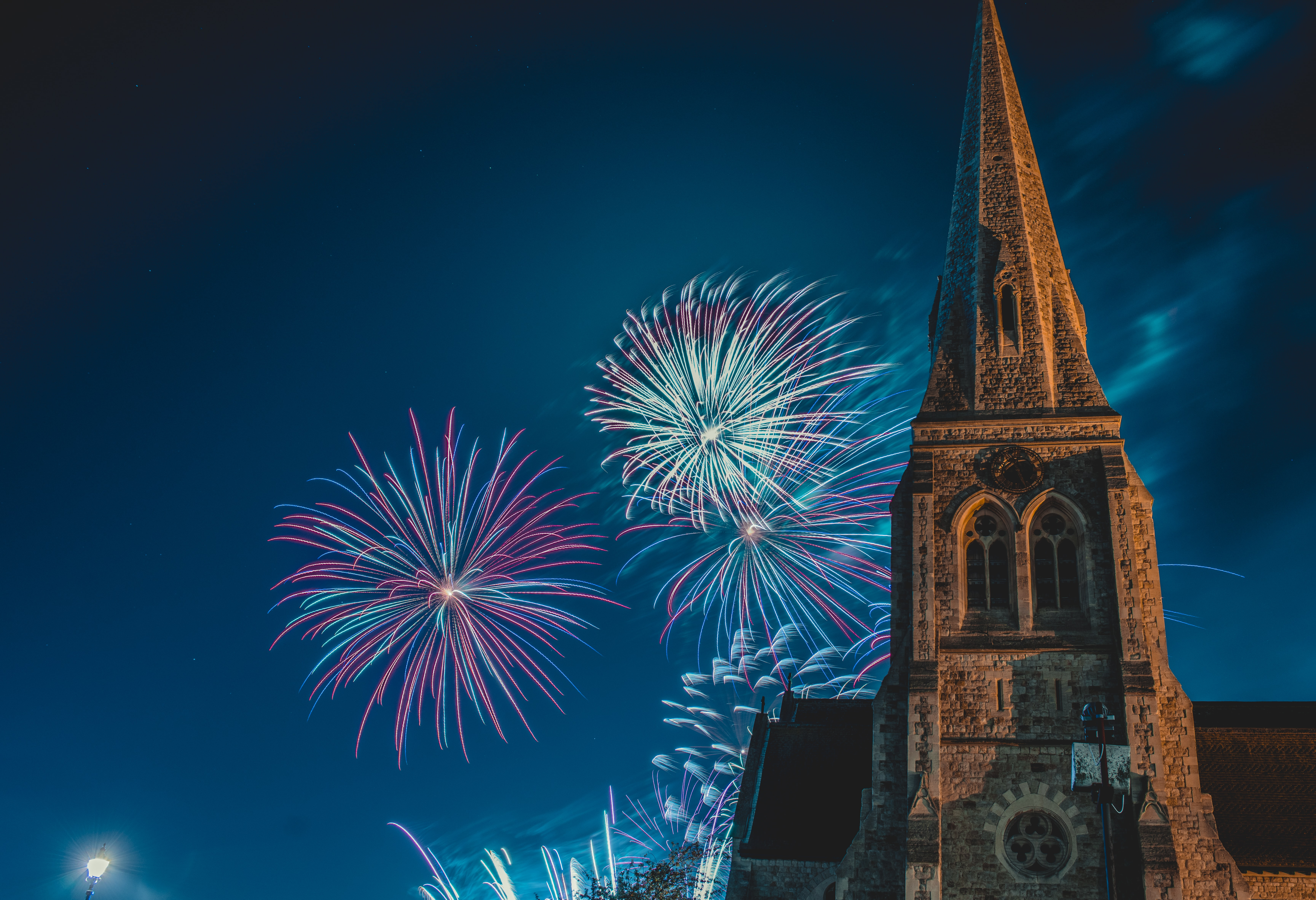 photo of pointed-edge church with fireworks