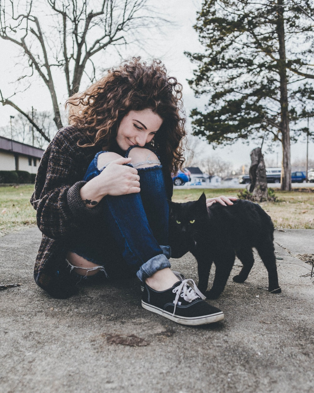woman sitting on ground while petting cat during daytime