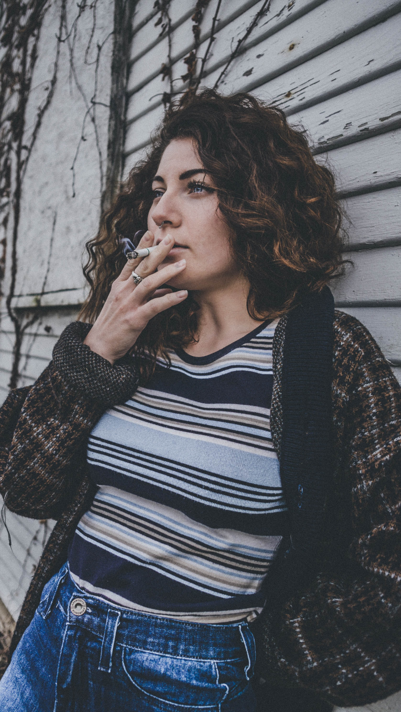 woman in brown and black jacket using cigarette
