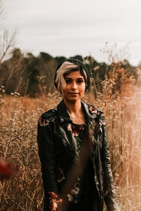 standing woman wearing leather jacket at the field during day