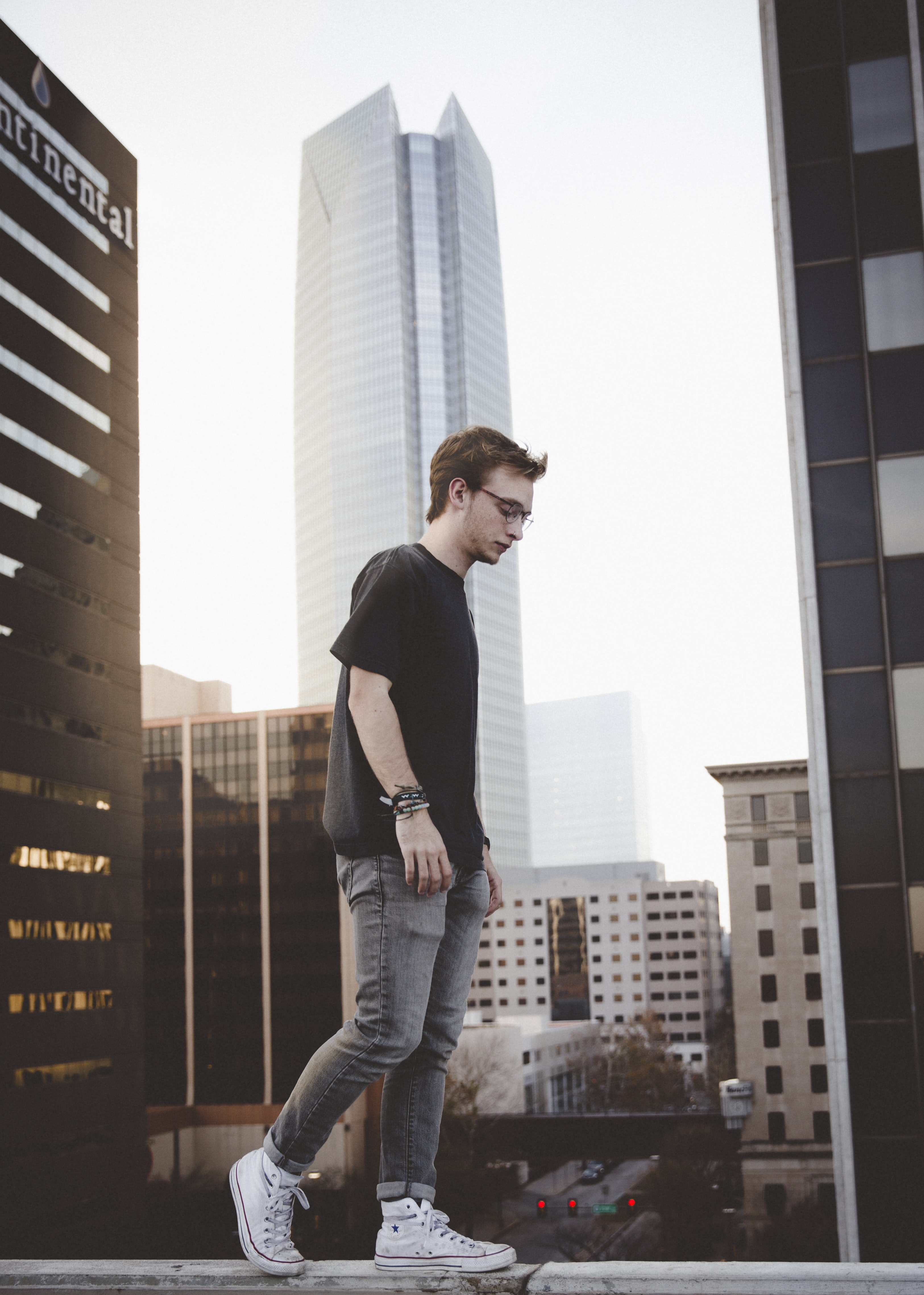 man standing on ledge surrounded by buildings